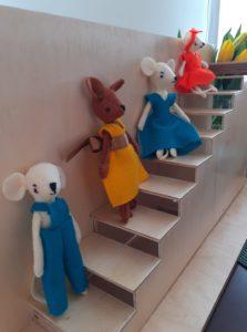 Filcowe myszki stoją na drewnianych schodach